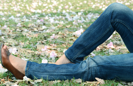 cropped shot: cropped shot of womans leg in jeans sitting on the grass at park Stock Photo