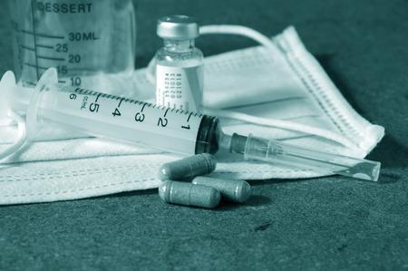 the syringe and medical mask photo