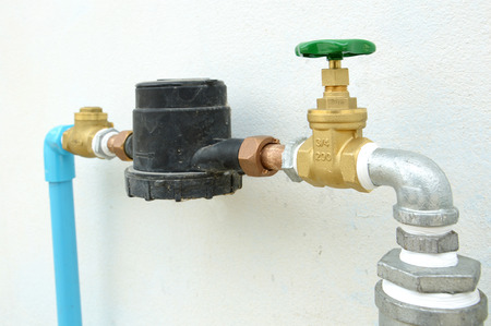 piping with a stopcock valve against a concrete wall Stock Photo