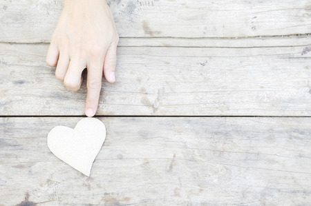 paper heart with woman hand on wood background