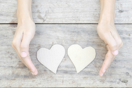 paper heart with woman hand on wood background photo