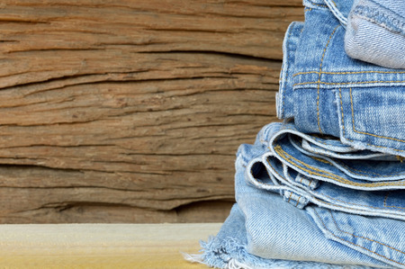 in jeans: gran cantidad de pantalones vaqueros azules sobre fondo de madera