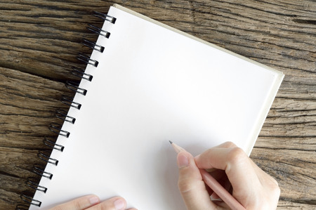 top view of hand writing on notebook on wooden table background
