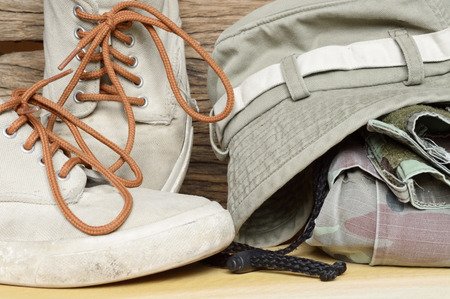 army pants and sneakers on wooden background Stockfoto