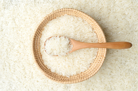 white rice in wicker basket with wooden spoon on rice background photo