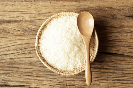 white rice in wicker basket with spoon on wooden background