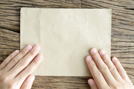 top view of woman hand and blank paper on wooden table background photo