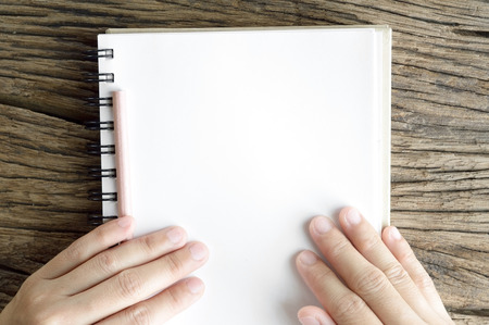 top view of woman hand and blank notebook on wooden table background photo
