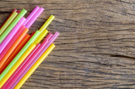drinking straw: colorito plastica cannuccia su fondo in legno Archivio Fotografico