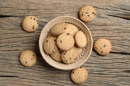 galleta de chocolate: galleta de chocolate en la cesta de mimbre en la mesa de madera Foto de archivo