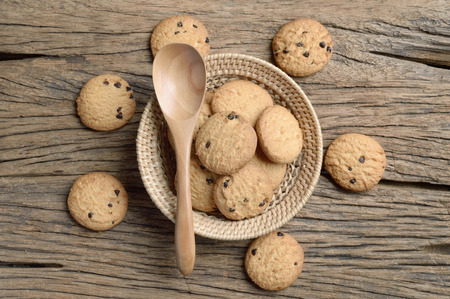 chocolate chip: chocolate chip cookie in wicker basket on wooden table