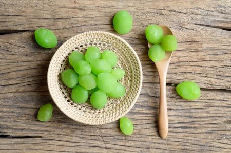 myrobalan: green pickle myrobalan fruit in wicker basket on wooden table