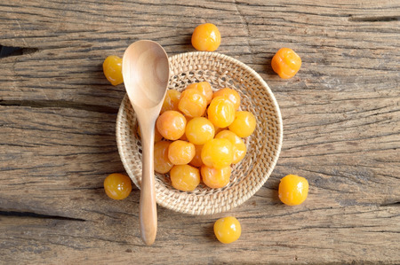 pickle: yellow pickle cherry fruit in wicker basket on wooden table Stock Photo
