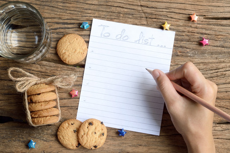 woman hand write to do list on wooden table with chocolate chip cookie