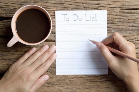 cheque en blanco: mano de la mujer de escritura para hacer la lista en la mesa de madera con la taza de café Foto de archivo