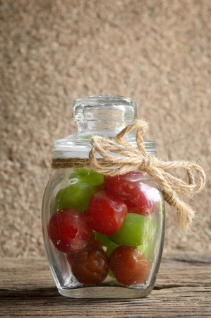 myrobalan: mix pickle cherry fruit in glass bottle on wooden table Stock Photo