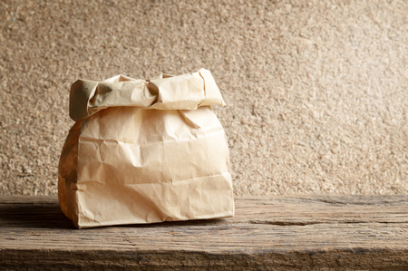 brown paper bag: brown paper bag on wooden background Stock Photo