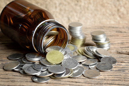 the thai: coins in glass bottle on wooden table, Thai baht