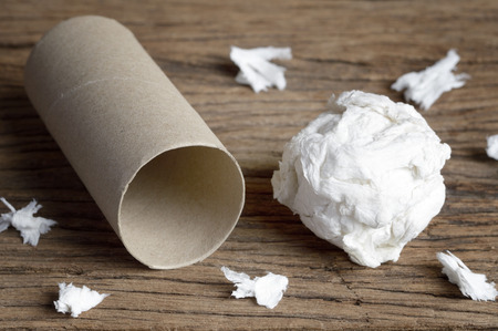 leftover: used paper tissue and leftover roll on wooden table Stock Photo