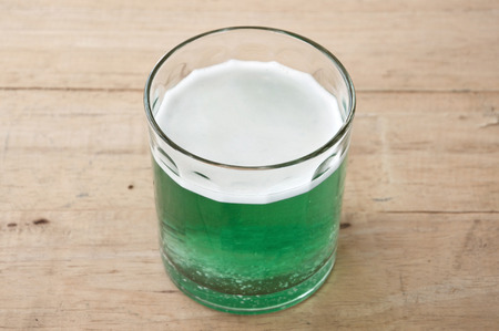 antacid: effervescent tablet dissolved in glass of water on wooden table