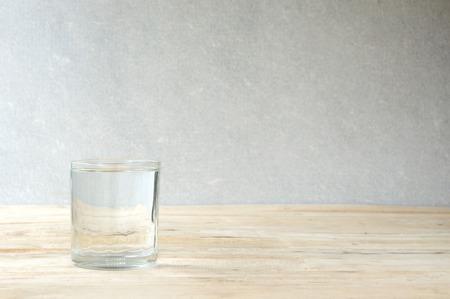 agua purificada: vaso de agua purificada en la mesa de madera - fondo de la pared de concreto