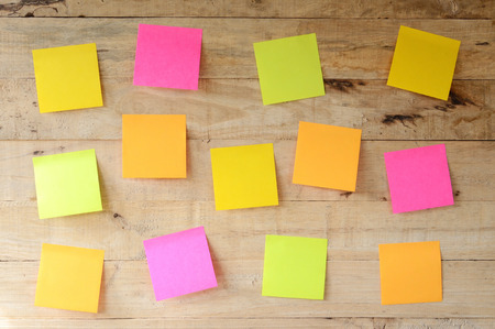 empty colorful sticky notes on wooden bulletin board, ready for message