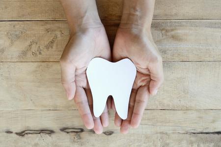 paper cut: paper cut teeth shape in woman hand Stock Photo