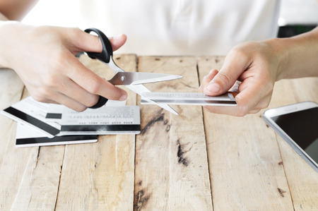 indebted: woman is cutting credit card with scissors over other credit cards on table because of big debt