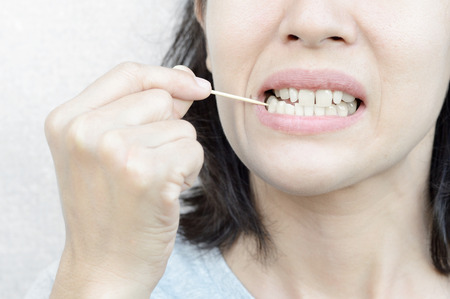 woman use wooden toothpick for cleaning teeth Reklamní fotografie - 106300143