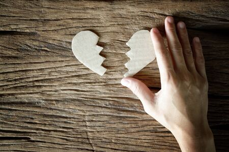 woman hand holding broken heart paper cut on wooden background - love concept