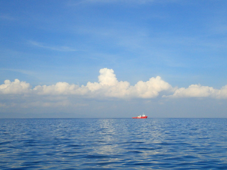 far away: blue sky and sea with far away red ship