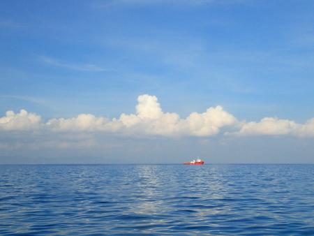 lejos: cielo azul y el mar con la nave lejos roja