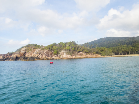 noon: blue sky and turquoise sea with rocky island Stock Photo