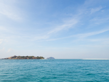 noon: sky and shallow sea with island Stock Photo
