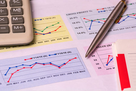 A closeup of a business financial chart with bar and pie graphs. A pen is on top. Can be used to represent business expenses, growth or revenue
