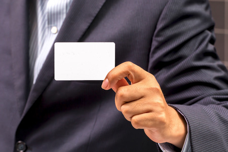 Business man handing a blank business card at his office Banco de Imagens