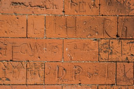the eighteenth: A red brick school wall covered with scratched eighteenth century graffiti for background or texture Stock Photo