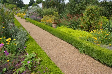 A gravel path in a beautiful english garden