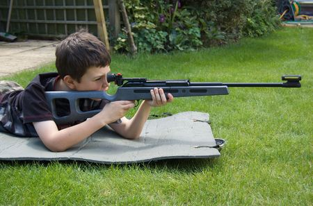 airgun: A young boy aims confidently with a target shooting air-rifle
