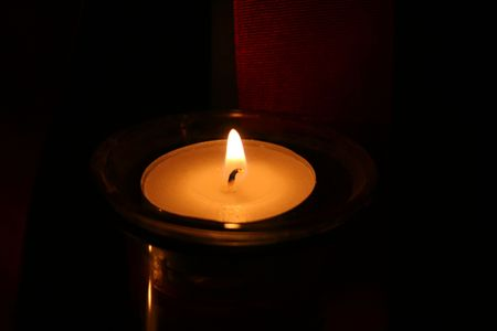 Lone candle glowing in the dark