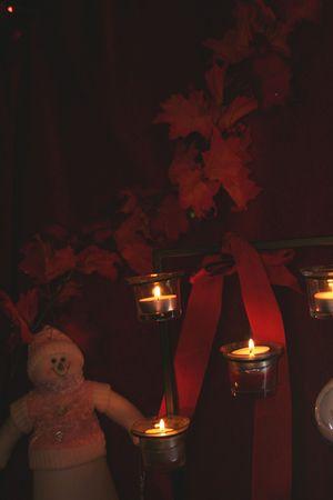 Snowman sitting near candle light