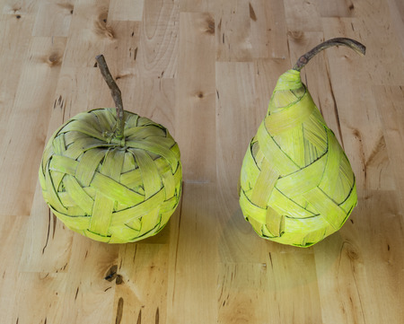 artefacts: Green pear and apple made from bast fibre laying on the wooden table Stock Photo