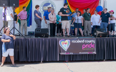 homosexuales: Nyack NY EE.UU. 14 de junio 2015: El orgullo del condado de Rockland. Grupo de los funcionarios y l�deres de la comunidad en el escenario. Traductor signlanguage antes de la etapa. Editorial