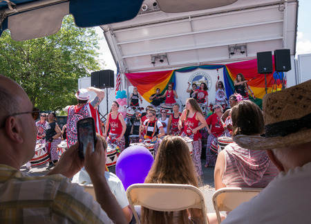 women only: Nyack NY USA  June 14 2015: Members of Batala NYC women only band with leader on the front performing before the stage during Rockland County Pride. Observer taking pictures with the phone.