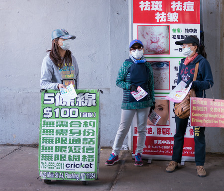 sidewalk sale: Flushing, New York - June 03 2015: Three girls wearing masks advertising different services in the street. Editorial