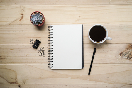 notebook design: Blank opened notebook with cup of coffee and memo note on wooden table. Top view. Writing concept