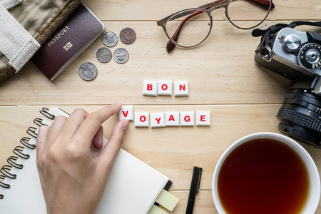 Outfit of traveler and word BON VOYAGE spelled using letter tiles on wooden background