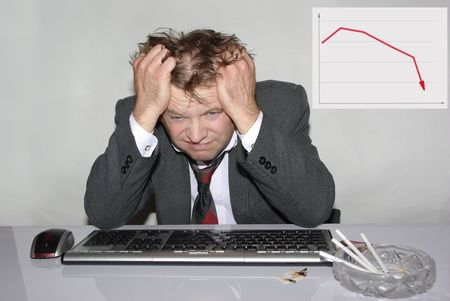 slump: stressed out man before computer and declining  graph