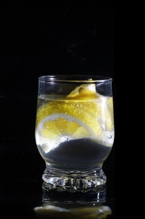 water with lemon in glass on a black background photo