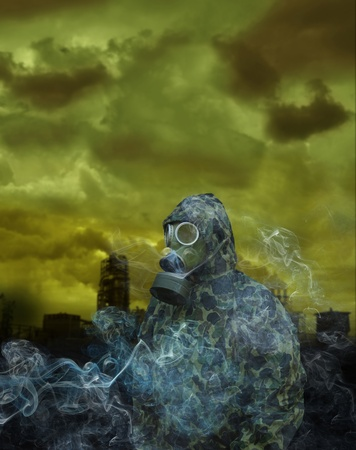 radiation protection suit: the man in anti-gas mask on a factory background Stock Photo